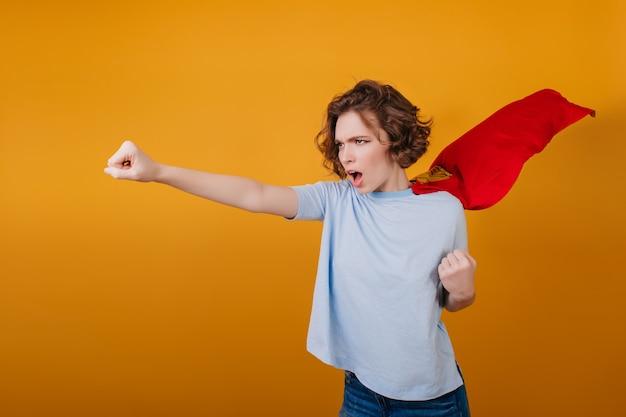 Garota confiante de cabelos curtos posando com uma capa vermelha de super-herói