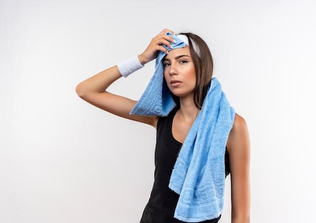 Garota confiante e muito esportiva usando bandana e pulseira, enxugando o suor da testa com uma toalha em volta do pescoço, isolada na parede branca