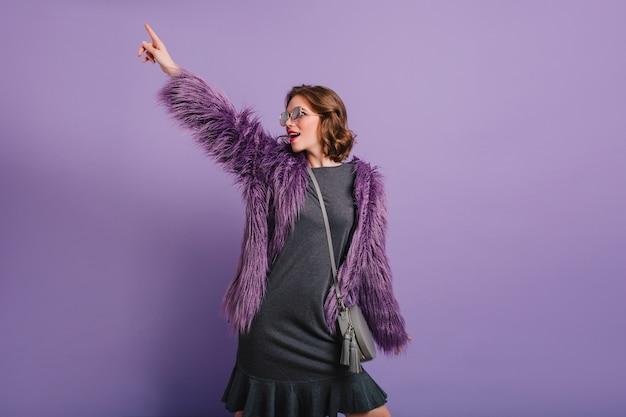 Garota confiante em um vestido preto da moda apontando o dedo e desviando o olhar no fundo roxo