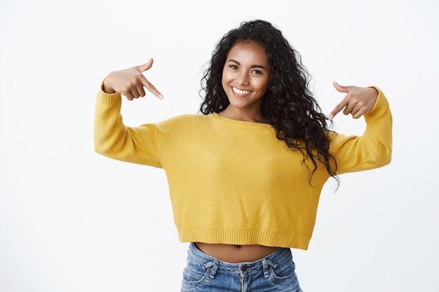 Garota confiante falando sobre si mesma, gabando-se de uma conquista incrível apontando para o peito e sorrindo, autoconfiante, exibindo-se orgulhosamente, parada em uma parede branca satisfeita, obtenha sucesso