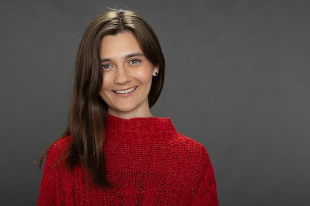 Garota confiante, positiva e sorridente, de cabelos compridos, posando de suéter vermelho