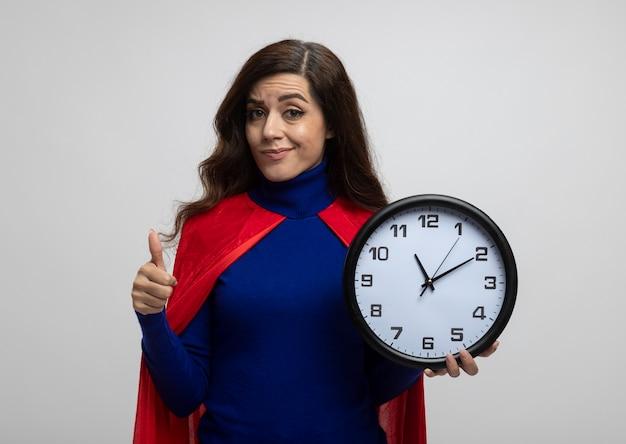 Garota confiante super-heroína caucasiana com capa vermelha polegares para cima e segurando o relógio isolado na parede branca com espaço de cópia