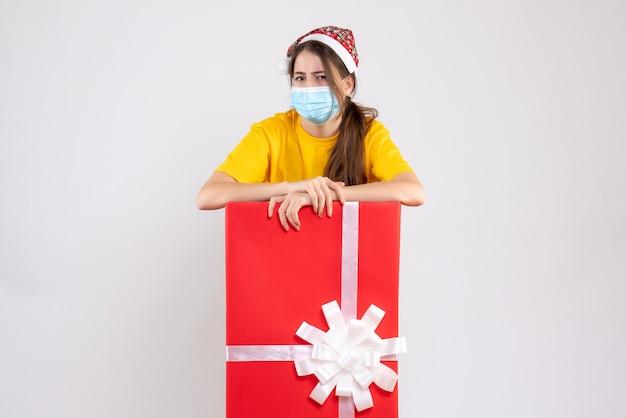 Garota confusa com um chapéu de papai noel atrás de um grande presente de natal