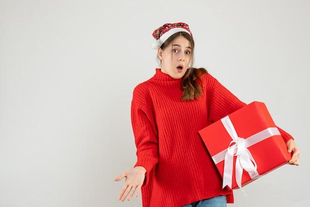 Garota confusa com um chapéu de papai noel segurando um presente de frente
