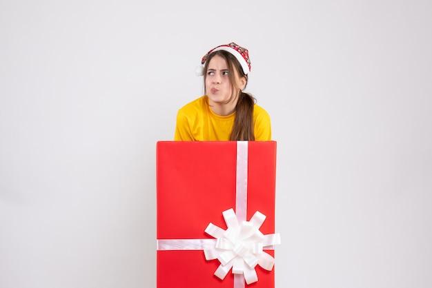 Garota confusa de frente com chapéu de papai noel atrás de uma grande caixa de presente
