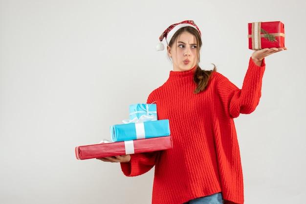 Garota confusa de frente com chapéu de papai noel comparando seu presente de natal