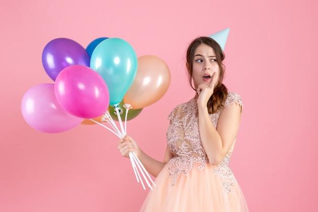 Garota confusa de vista frontal com boné de festa segurando balões