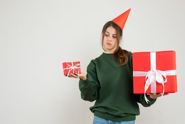 Garota confusa de vista frontal com chapéu de festa olhando para seu presente de natal