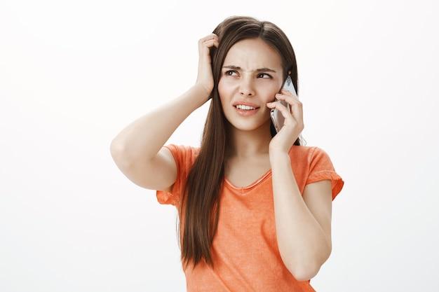 Garota confusa e insegura, parecendo intrigada no canto superior esquerdo enquanto fala no celular