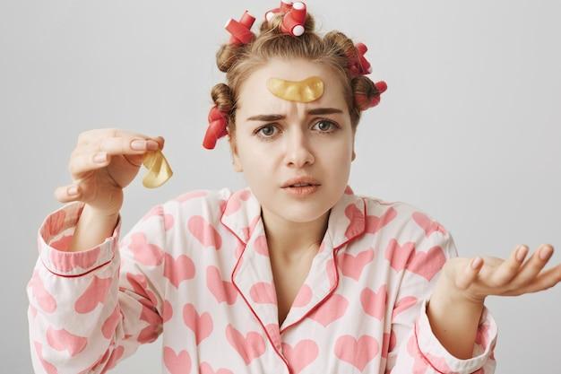 Garota confusa usando babadores de cabelo e pijama tentando aplicar tapa-olhos
