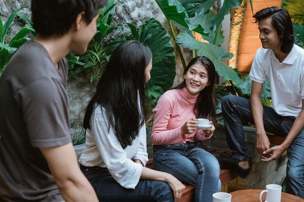 Garota conta histórias e seus amigos ouvem enquanto está sentada em uma mesa e um banco de madeira no jardim da casa
