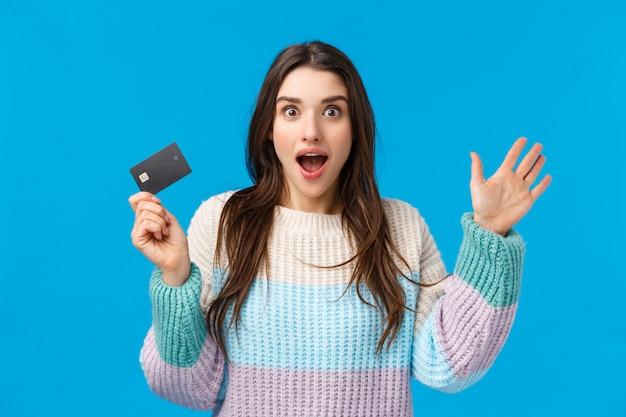 Garota contando notícias incríveis, explicando algo apaixonadamente e animada, gesticulando segurando o cartão de crédito, não posso expressar espanto e alegria, vendo algo de tirar o fôlego, digamos, pegue meu dinheiro