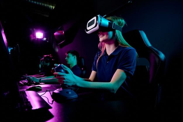 Garota contemporânea eenage em um fone de ouvido vr usando joystick enquanto está sentada em frente ao monitor do computador e jogando novo videogame no clube