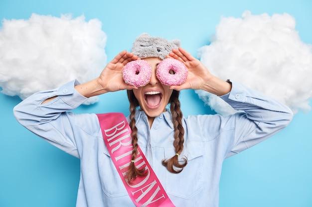 Garota contras olhos com rosquinhas vitrificadas mantém a boca aberta vestida de camisa com fita e se diverte no aniversário isolado no azul