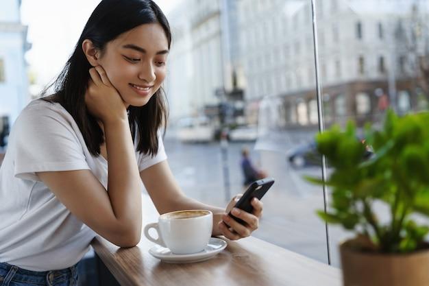Garota conversando no smartphone e tomando café em um restaurante perto da janela, sorrindo para a tela do celular