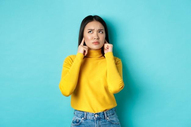 Garota coreana irritada reclamando dos vizinhos barulhentos, fechava as orelhas com os dedos e parecia zangada, de pé contra um fundo azul.