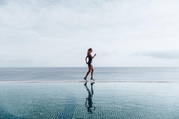 Garota corre ao longo da piscina. manhã correndo.