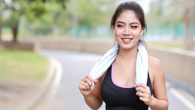 Garota corredora se exercitando ao longo de um caminho de concreto ao ar livre com um fundo de árvore verde