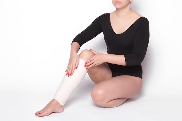 Garota corrige um curativo elástico na perna
