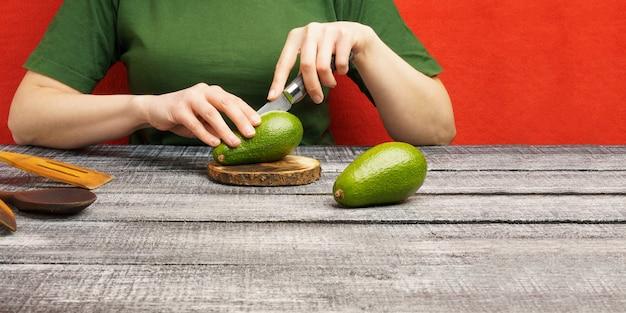 Garota corta abacate em uma placa redonda. a garota corta um abacate verde maduro com uma faca. os frutos são cortados em uma tábua de madeira.