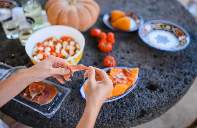 Garota cozinhando presunto italiano e aperitivo de melão culinária italiana