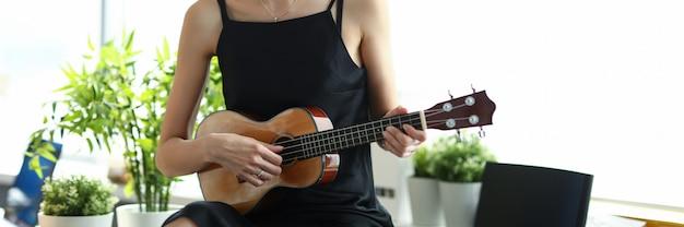Garota criativa em um vestido preto toca guitarra