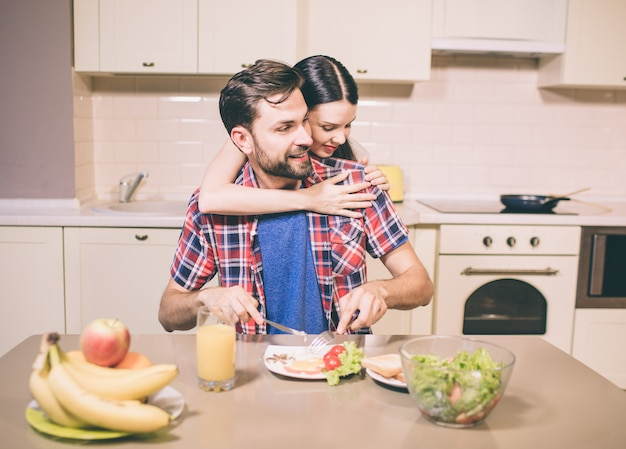 Garota cuidadosa está por trás do cara e abraçá-lo. ele olha para a direita e sorri um pouco. ele corta a refeição no prato. o homem está comendo.