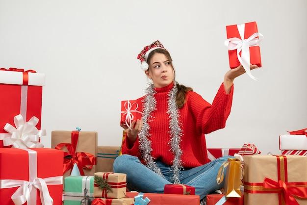 Garota curiosa com chapéu de papai noel segurando presentes sentados em volta de presentes