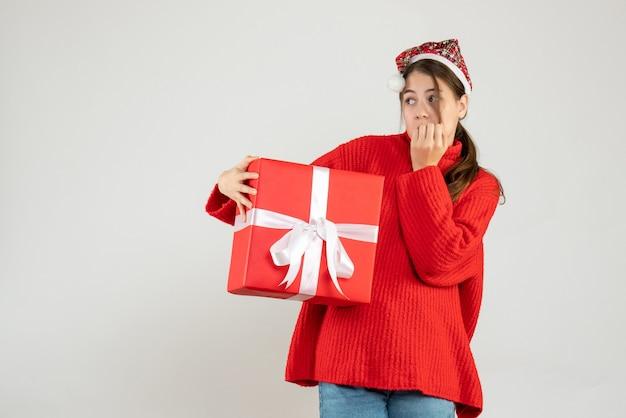Garota curiosa com chapéu de papai noel segurando um presente olhando para a esquerda