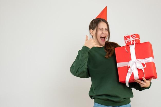 Garota curiosa de vista frontal com chapéu de festa fazendo um gesto de ligar para mim segurando seus presentes de natal