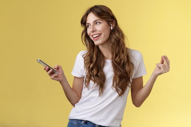 Garota curtindo música ouvindo música fones de ouvido sem fio dançando animada, despreocupada, olhando para longe sorrindo amplamente segurar smartphone encontrado nova faixa festejando sozinho trilha sonora filme favorito fundo amarelo