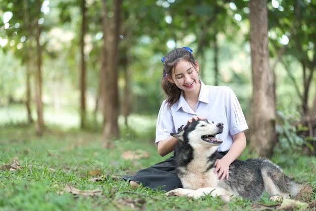Garota da ásia vestindo uniforme brincando com um husky siberiano
