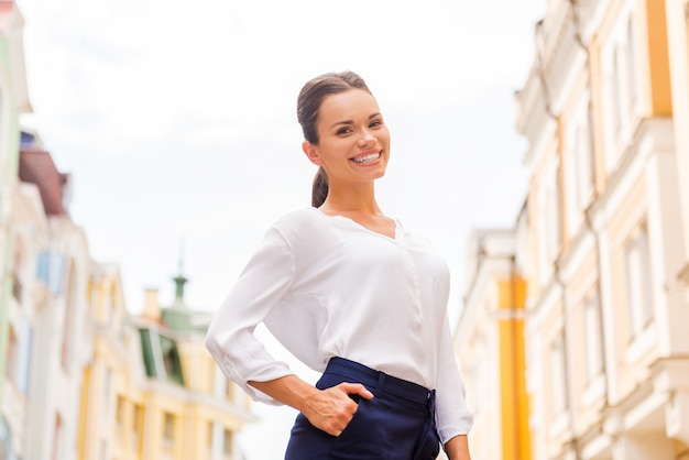 Garota da cidade. mulher jovem e atraente segurando a mão no bolso e sorrindo em pé na rua