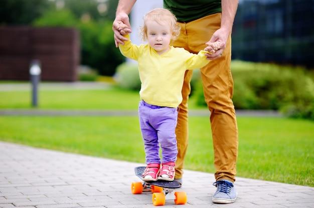 Garota da criança aprendendo a andar de skate com o pai