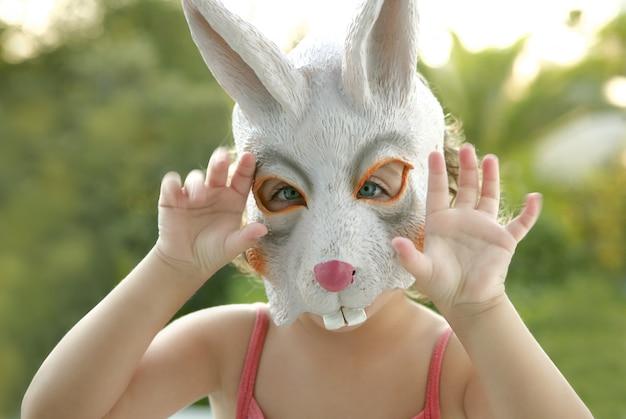 Garota da criança com máscara de coelho branco