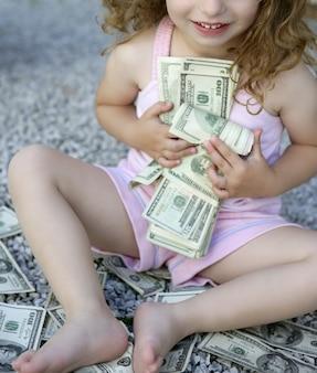 Garota da criança com muitas notas de dólar