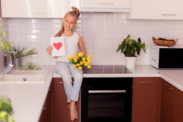Garota da criança com um buquê de flores e um cartão postal sentado na cozinha.