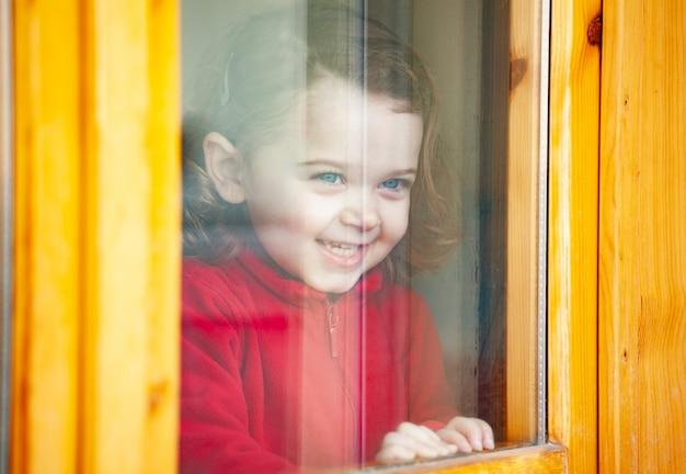 Garota da criança olhando pela janela.