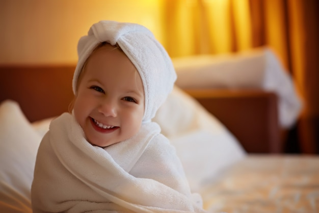 Garota da criança vestindo roupão após o banho
