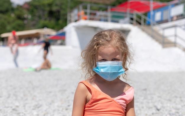 Garota da criança vestindo uma máscara protetora na praia
