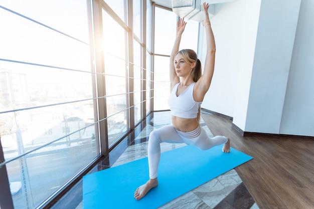 Garota da ioga em pose de guerreiro dentro de casa