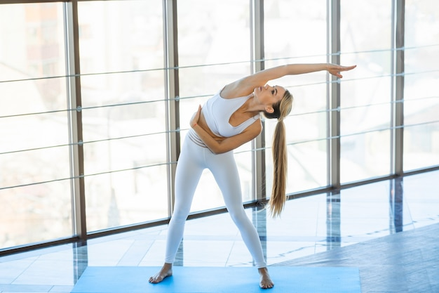 Garota da ioga fazendo esportes dentro de casa