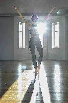 Garota da manhã ioga fazendo exercícios de alongamento na sala de pilates
