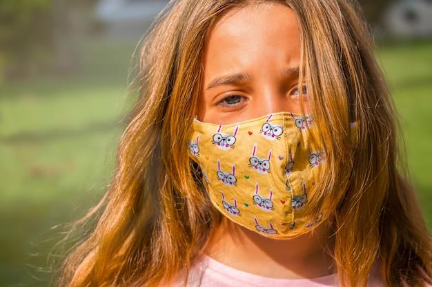Garota da máscara facial caminha no parque durante o dia.