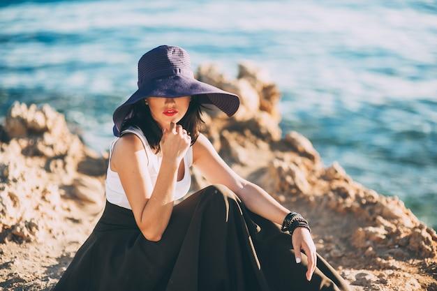 Garota da moda em um grande chapéu posando em uma pedra na praia