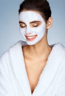 Garota da risada com máscara facial hidratante