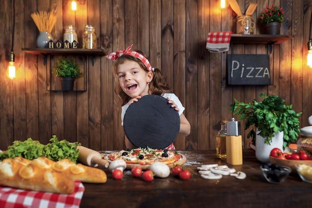 Garota da risada com tábua redonda cozinhar pizza deliciosa