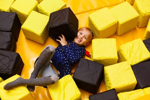 Garota da risada feliz brincando com brinquedos, bolas coloridas no playground, poço de bola, piscina seca.