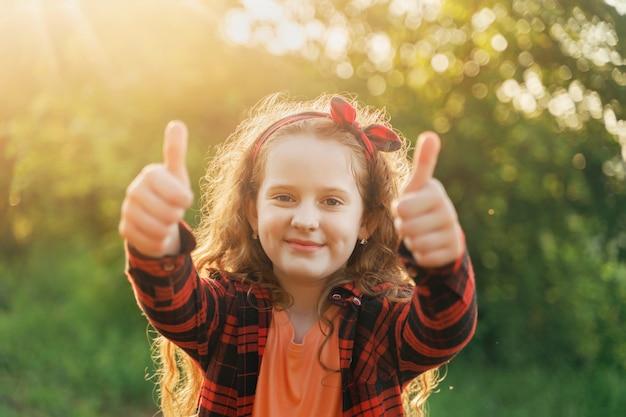 Garota da risada mostrando os polegares.