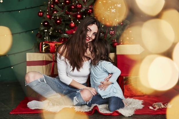 Garota dá um beijo. alegre mãe e filha sentada perto da árvore de natal que por trás